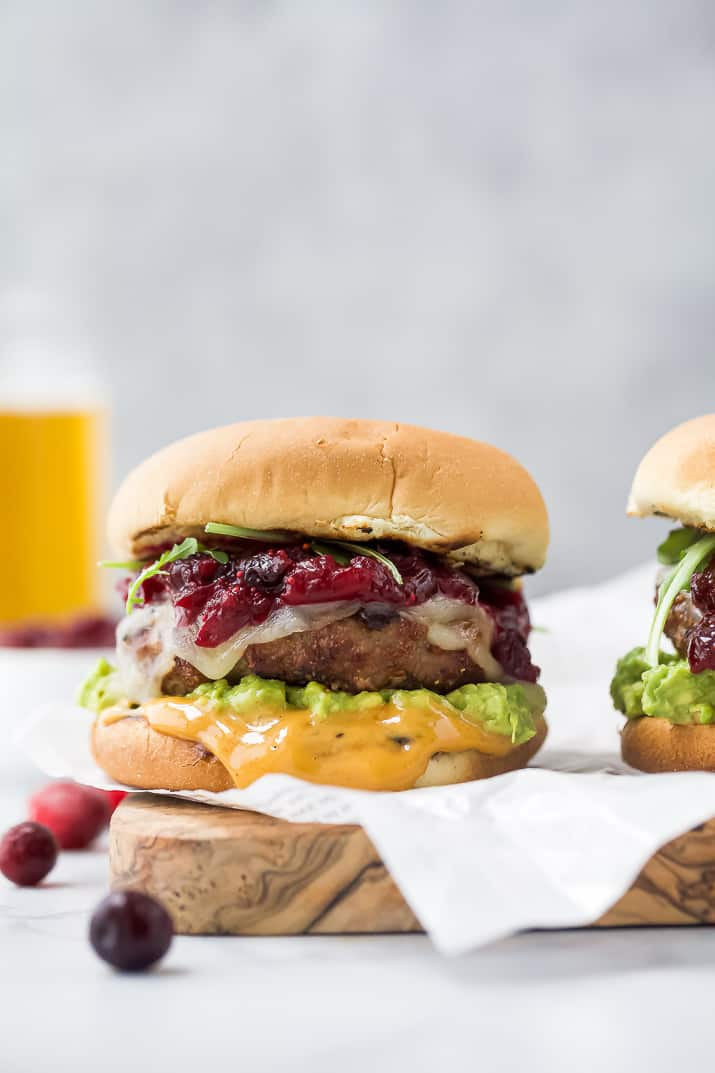 avocado turkey burger topped with cranberry chutney on a cutting board
