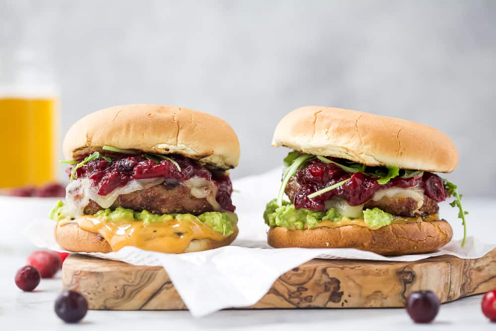 two avocado turkey burgers topped with cranberry chutney