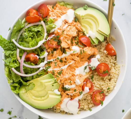 A close-up shot of a buffalo chicken quinoa bowl topped with chopped cilantro and ranch dressing