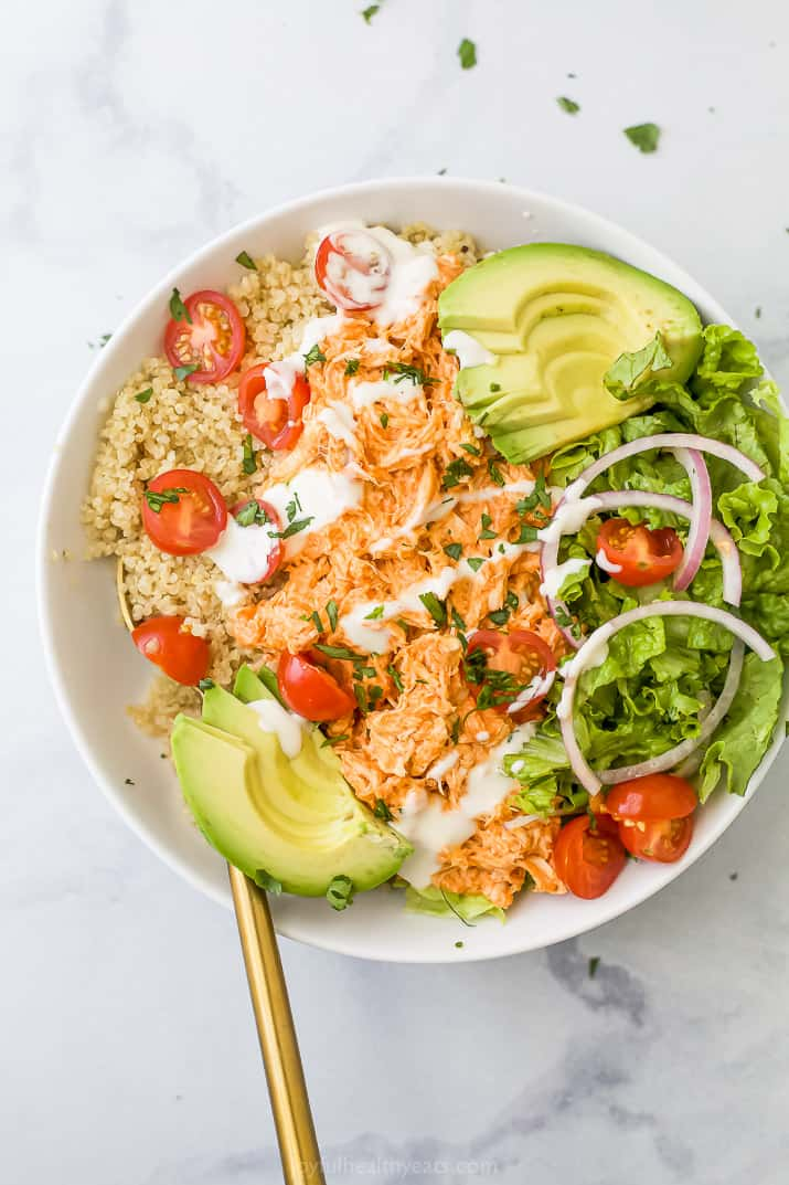 A buffalo chicken quinoa bowl on a granite surface with a golden spoon inside