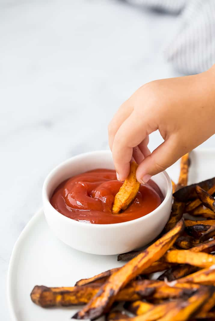 dunking a sweet potato fry into ketchup