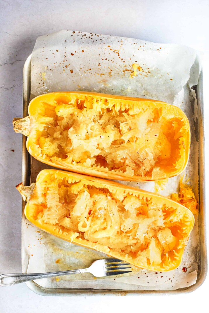 Cooked spaghetti squash on a lined baking sheet with a metal fork