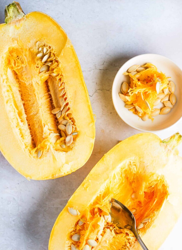 Two halves of a spaghetti squash on a countertop with a spoon scraping out the seeds