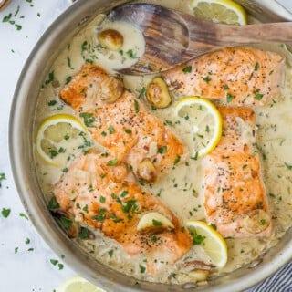 pan seared salmon with garlic cream sauce in a pan