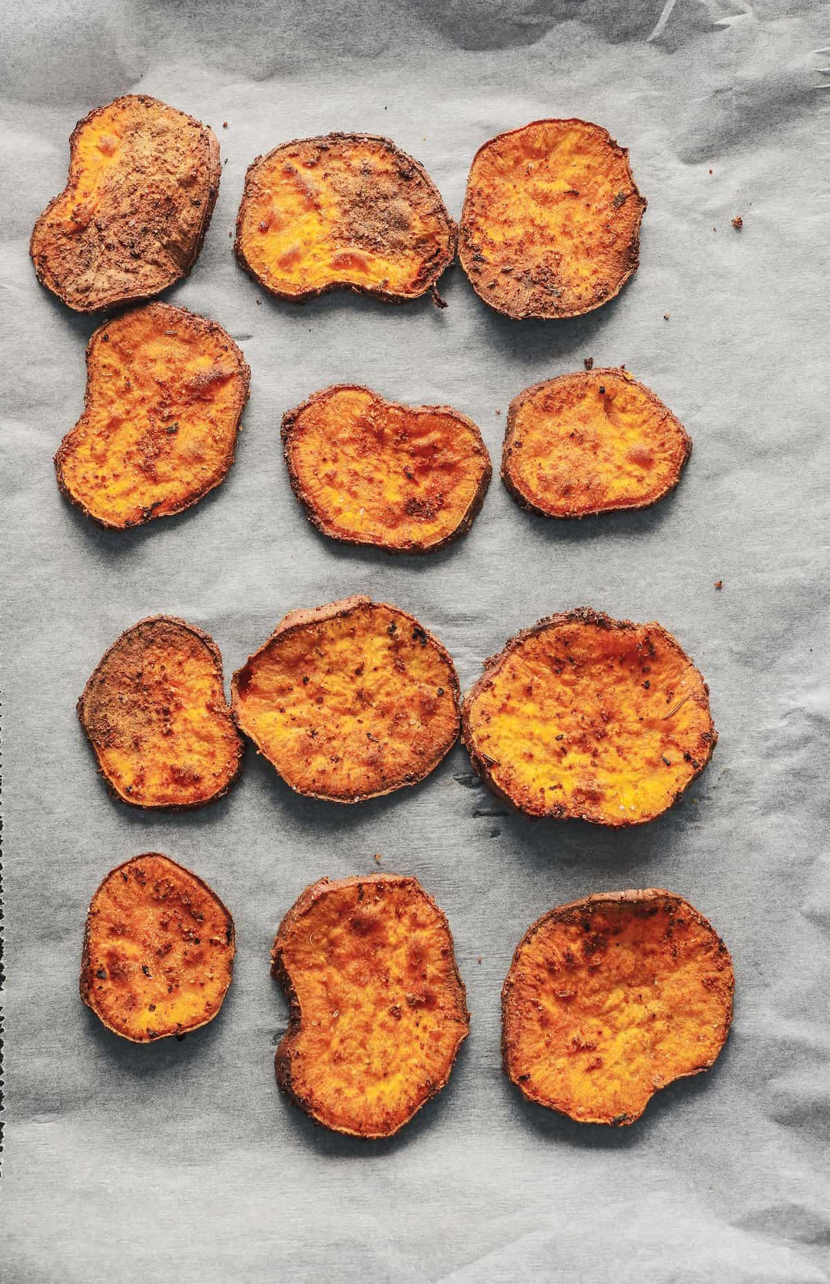 Twelve flat sweet potato fries on a baking dish lined with parchment paper