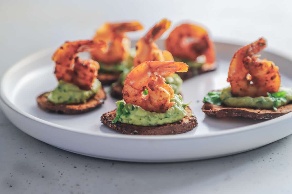 A close-up shot of six cajun shrimp sweet potato bites on a rimmed plate