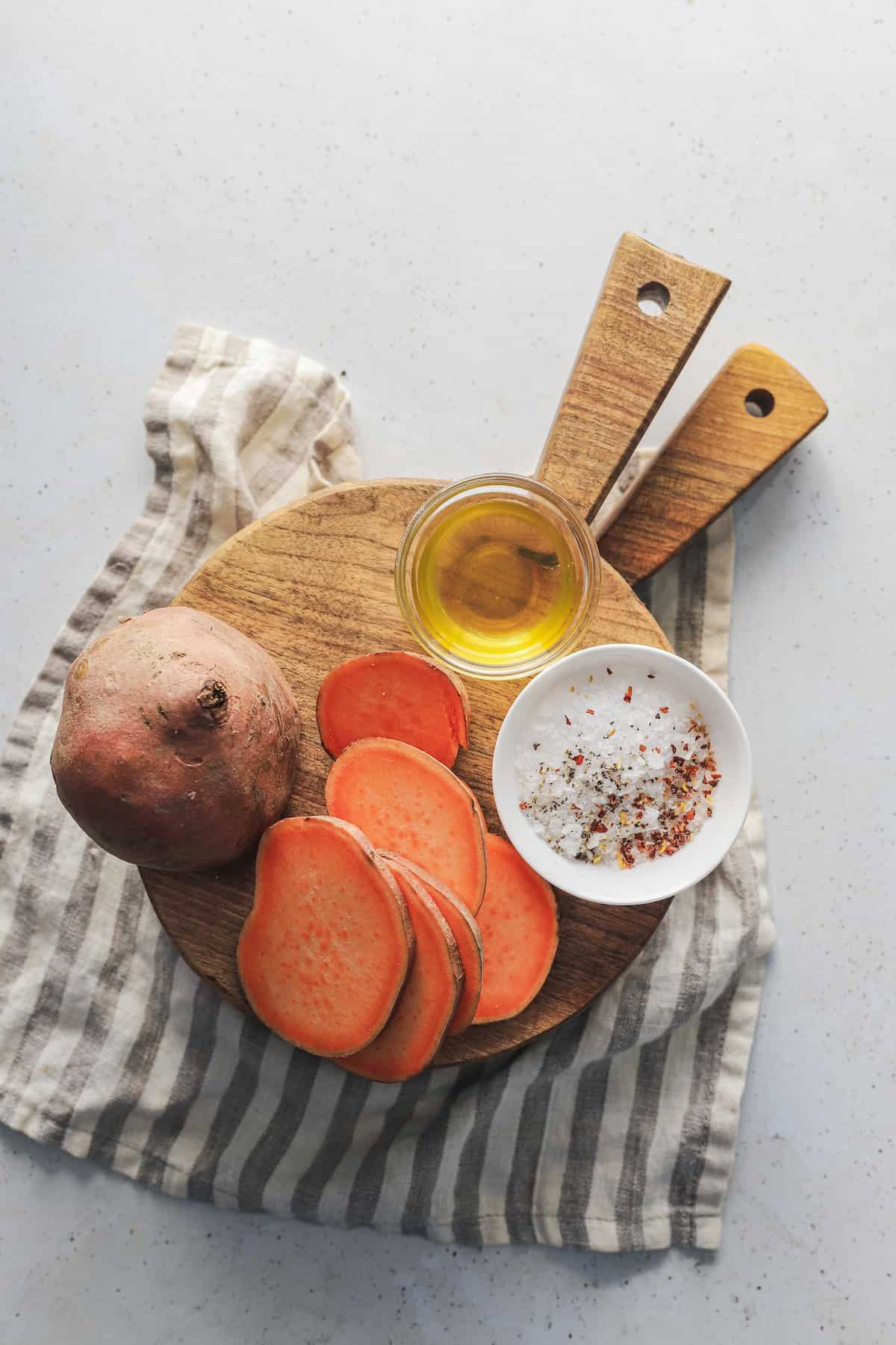 Sliced sweet potato on a wooden stand beside a dish of oil and a dish of salt