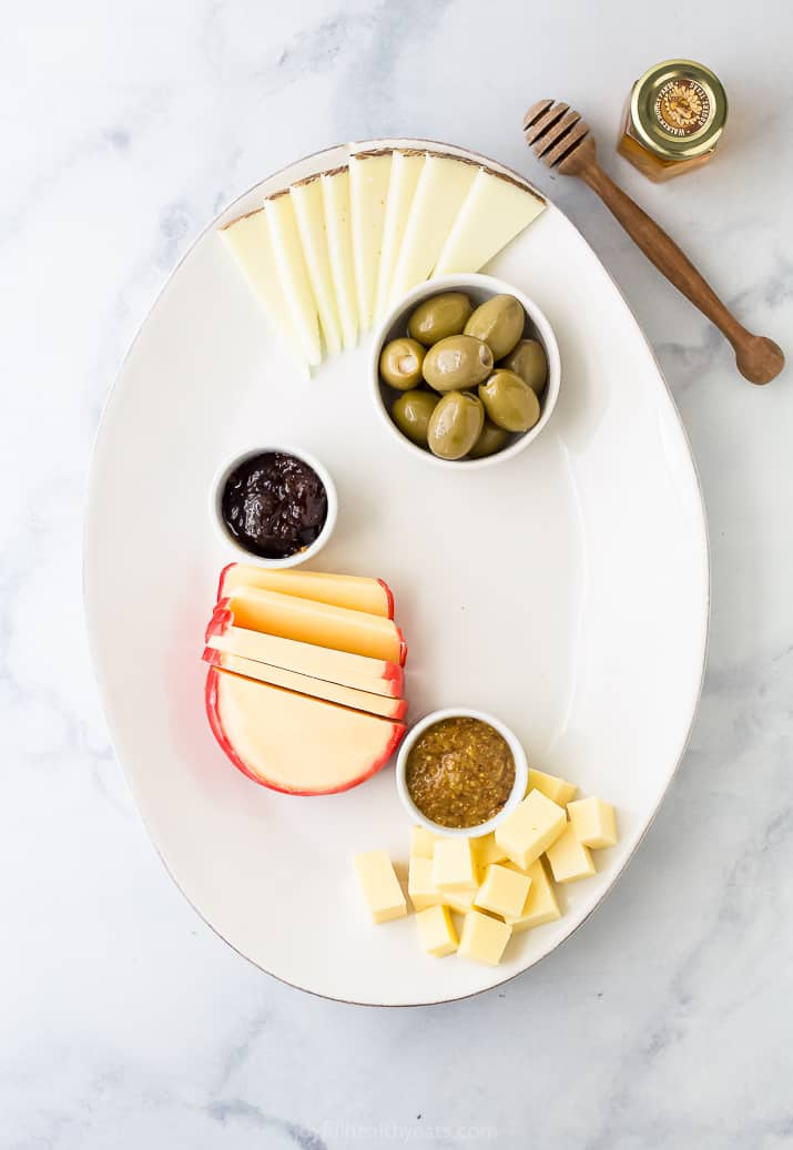 cheese board platter with cheese and condiments