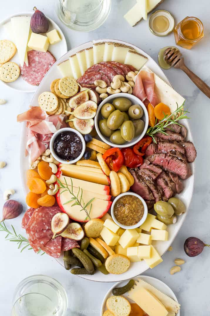 charcuterie board for two with plates and wine surrounding