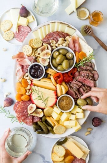 charcuterie board for two with hands grabbing from the board