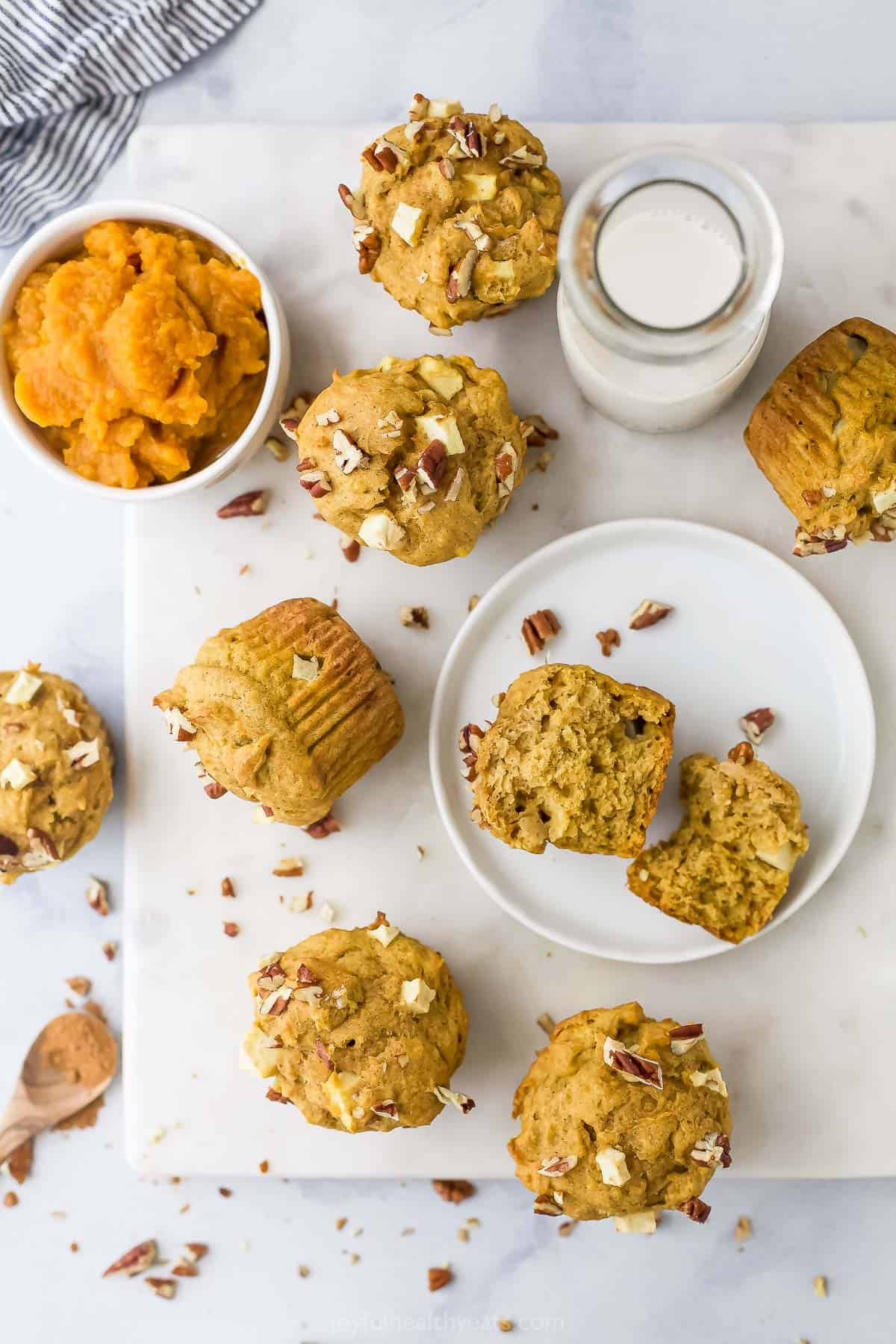 Apple pumpkin muffins scattered across a kitchen counter alongside a glass of milk and a bowl of pumpkin puree