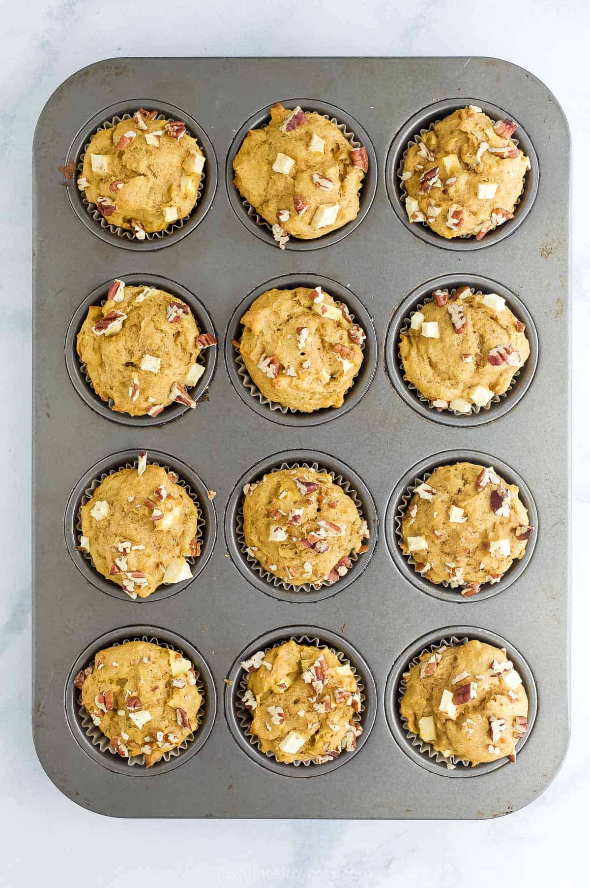 An overhead shot of a twelve-count cupcake tin filled with baked muffins