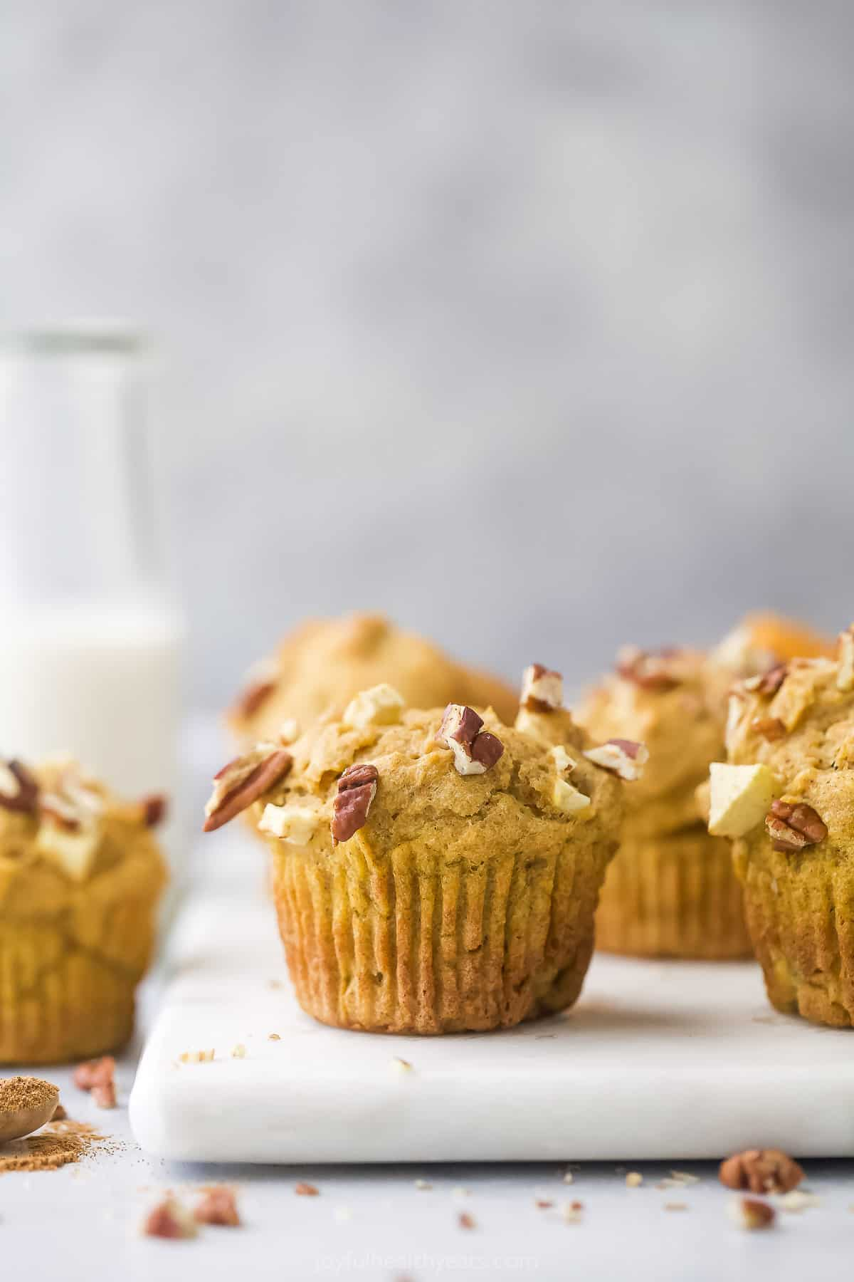 A white cutting board holding freshly baked apple pumpkin muffins with chopped pecans on top