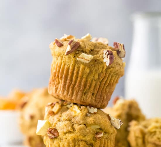 Two apple pecan muffins stacked on top of one another with a glass of milk behind them