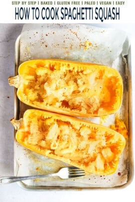 Two scraped spaghetti squash halves on a baking sheet lined with parchment paper