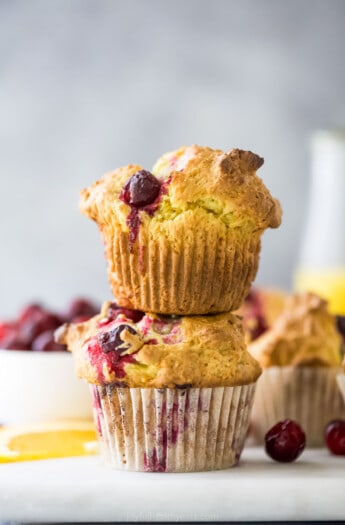A close-up shot of a stack of two cranberry orange muffins on top of a cutting board