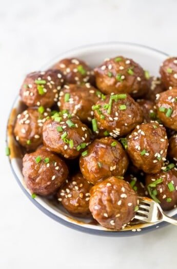 Crockpot Asian meatballs piled into a small bowl with a fork stabbing into one of them