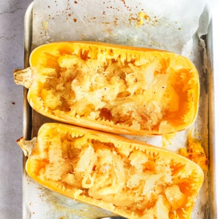 Two halves of a baked spaghetti squash on a parchment-lined pan with a fork