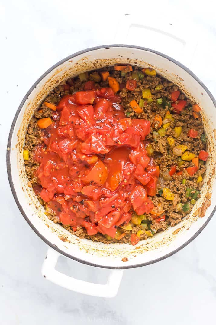 dutch oven filled with beef vegetables and diced tomatoes for chili